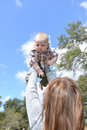 Baby outdoors in summer with mom playing by flying him through the air Royalty Free Stock Images