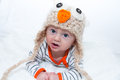 Baby in owl hat lying on his stomach playing Stock Photography