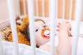 Baby with pacifier in white bed Royalty Free Stock Photo