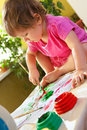 Baby painting with paint brush beautiful girl sitting on the table covered in bright and Stock Images