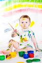 Baby and paints little girl bedaubed with bright colors Royalty Free Stock Images
