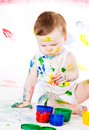 Baby and paints little girl bedaubed with bright colors Stock Image