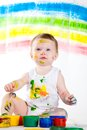Baby and paints little girl bedaubed with bright colors Royalty Free Stock Image