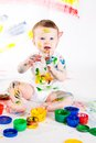 Baby and paints little girl bedaubed with bright colors Stock Photography