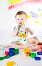 Baby and paints little girl bedaubed with bright colors Royalty Free Stock Photo