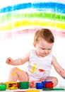 Baby and paints little girl bedaubed with bright colors Stock Images