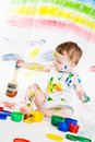 Baby and paints little girl bedaubed with bright colors Stock Photos
