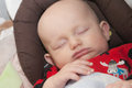 Baby peacefully sleeping a newborn boy quietly wearing a red sleep and play with a moose on it Stock Photo