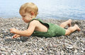 Baby on pebble beach Stock Photo