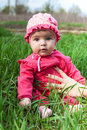 Baby in a pink dress suit sits among green grass supported maternal hand outdoors Royalty Free Stock Image