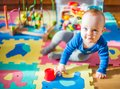 Picture : Baby play in his room, many toys islands  surrounded