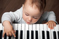 Baby play music on piano keyboard portrait of little child black and white Royalty Free Stock Images