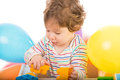 Baby playing with building blocks and sitting in a chair colorful balloons Royalty Free Stock Photo