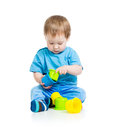 Baby playing with colourful cup toys on floor Stock Images