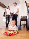 Baby Playing on Floor with Parents in Background Stock Photo