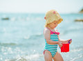 Baby playing with pail near sea Royalty Free Stock Photo