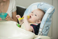 Baby playing with spoon while eating Royalty Free Stock Photo