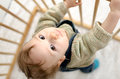 Baby in the playpen little boy looks into camera Stock Photo
