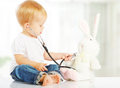 Baby plays in doctor toy bunny rabbit and stethoscope Royalty Free Stock Photo