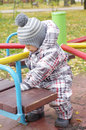Baby plays outdoors in autumn on playground age of year Royalty Free Stock Photography