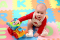 Baby plays with toy car on colourful puzzle tiles Stock Images