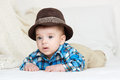 Baby portrait lie on white towel in bed, dressed in plaid shirt and hat Royalty Free Stock Photo