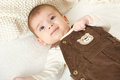 Baby portrait lie on white towel in bed, yellow toned Royalty Free Stock Photo