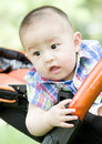 A baby in pram chinese is sitting outdoor Stock Image