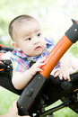 A baby in pram chinese is sitting outdoor Stock Photography