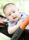 A baby in pram chinese is sitting outdoor Royalty Free Stock Photo