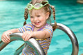Baby in protective goggles leaves pool. Stock Photography