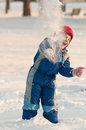 Baby pulling snowballs child playing at throwing Royalty Free Stock Image