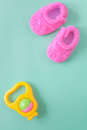 Baby rattle and booties on green background Royalty Free Stock Photo