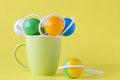 Baby rattle in cup on yellow background Royalty Free Stock Photo