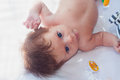 Baby with rattle lie toy and and look in camera Stock Photos