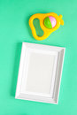 Baby rattle and photo frame on green background Royalty Free Stock Photo