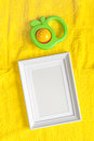 Baby rattle and photo frame on yellow background Royalty Free Stock Photo