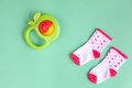 Baby rattle and socks on green background Royalty Free Stock Photo