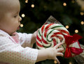 Baby reaching for Christmas Candy Cane Lollipop Royalty Free Stock Photography