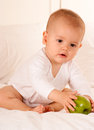 Baby reaching for a green apple Stock Photo