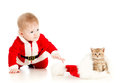 Baby reaching out hand for cat in santa claus hat Stock Image