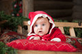 Baby in red clothes christmas time lying on pillow Royalty Free Stock Image