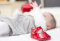 Baby red shoes and babe playing on the background closeup of patent leather over a bed adorable Stock Image