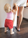 Baby red shorts clutching mom leg in kitchen