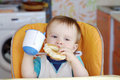 Baby with round cracknel and cup of tea happy boy age year on kitchen Stock Photography
