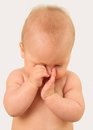 Baby rubbing s eyes feeling sleepy Stock Photo