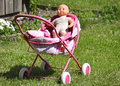 Baby s doll in a carriage on grass Royalty Free Stock Photo