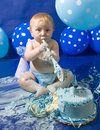 Baby s first birthday cake smash party a boy playfully covering his mother in Stock Photo