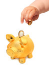 Baby s hand with coin and piggybank isolated over white Royalty Free Stock Photo