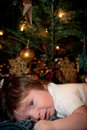 Baby s holiday stress a with a scared expression laying down under a christmas tree the image has a vertical orientation and copy Stock Image